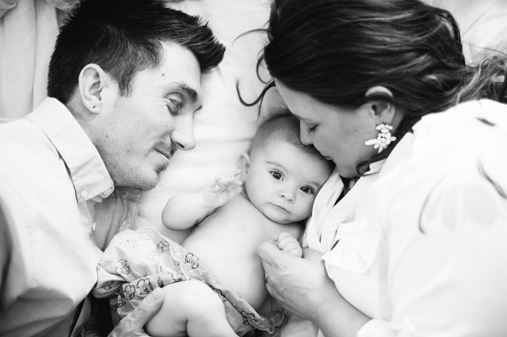 black and white photo of couple cuddling with their baby