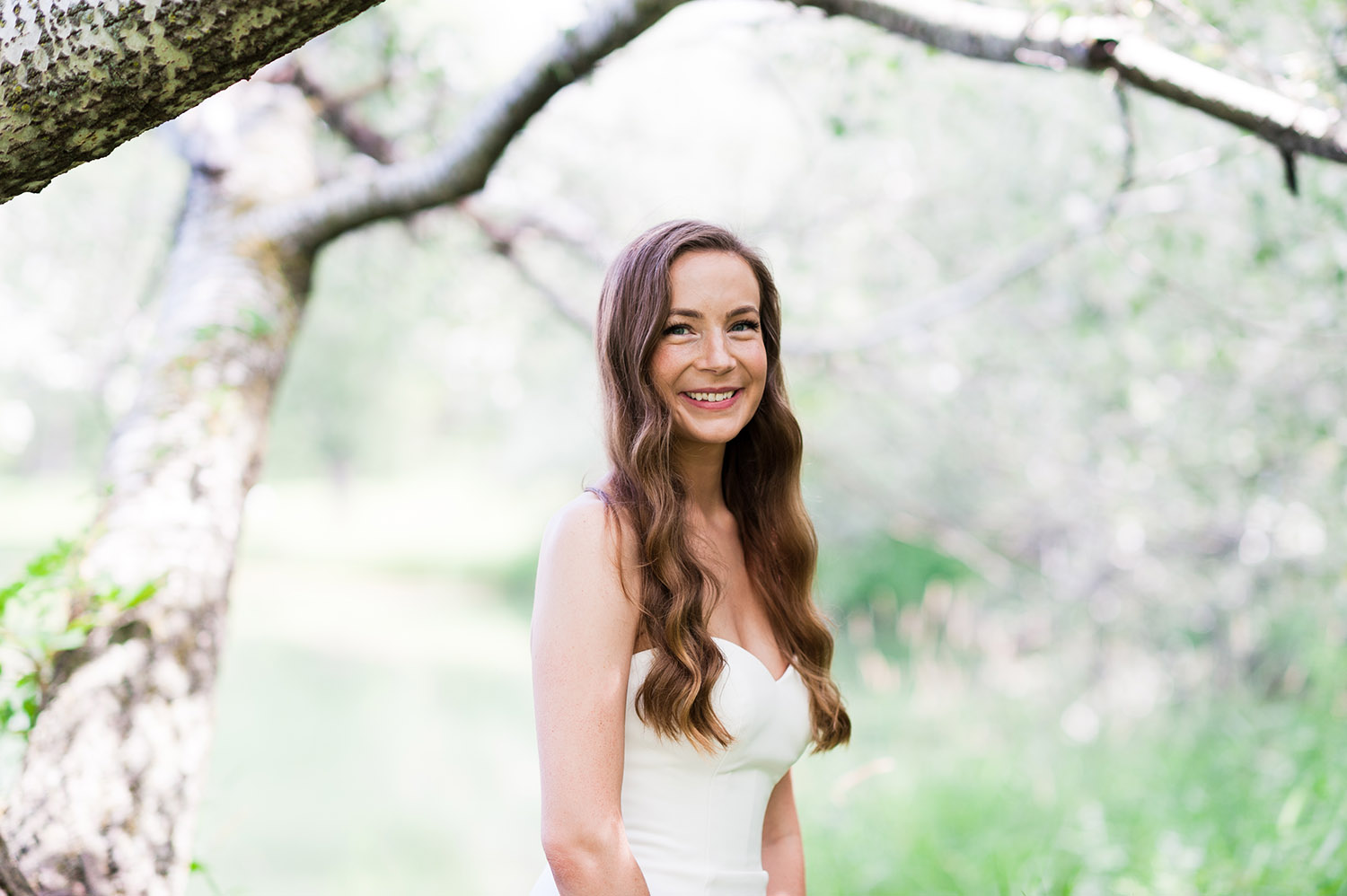 bride with long, dark wavy hair in nature