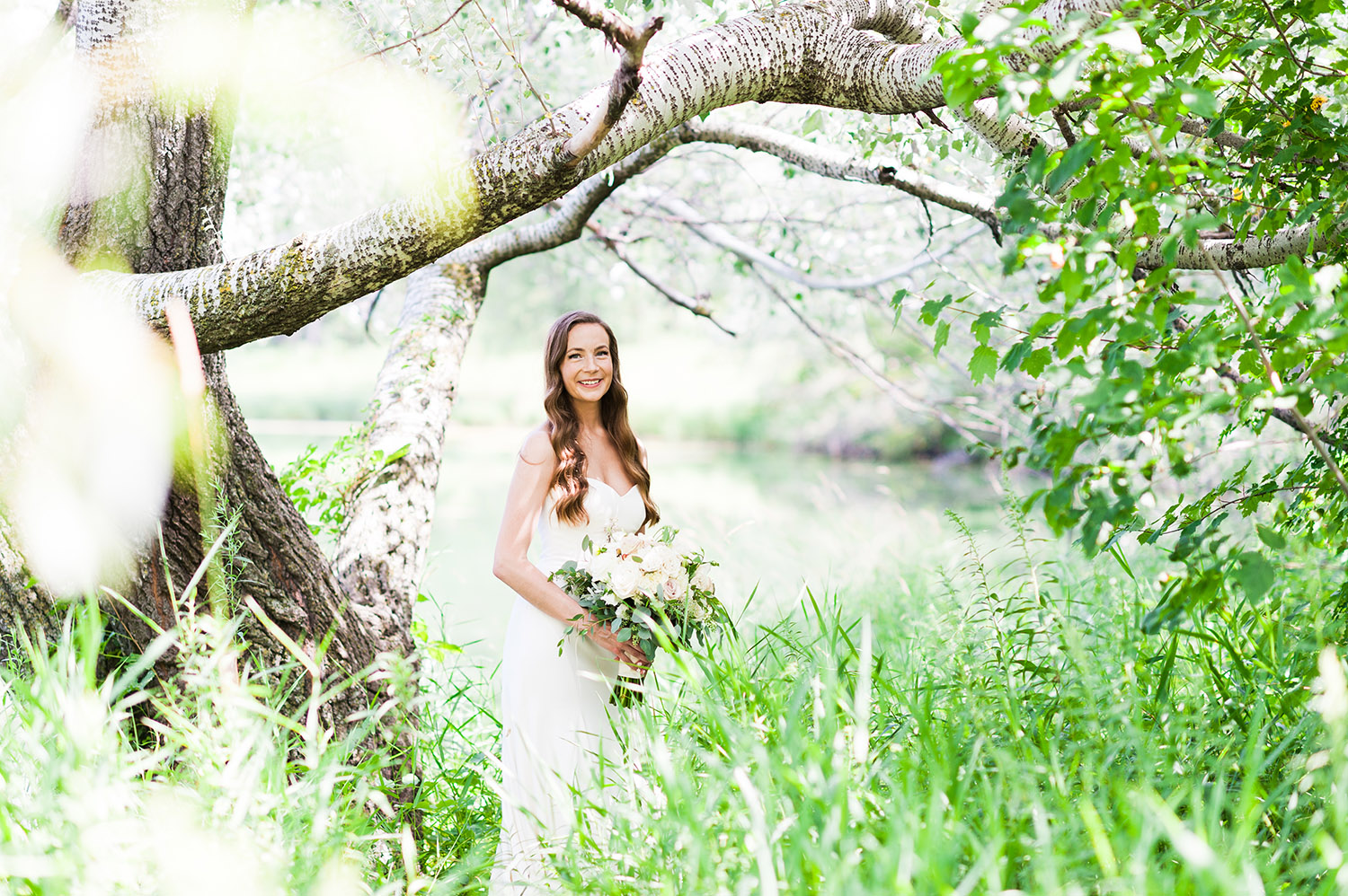 bride with long, dark wavy hair in nature with bouquet