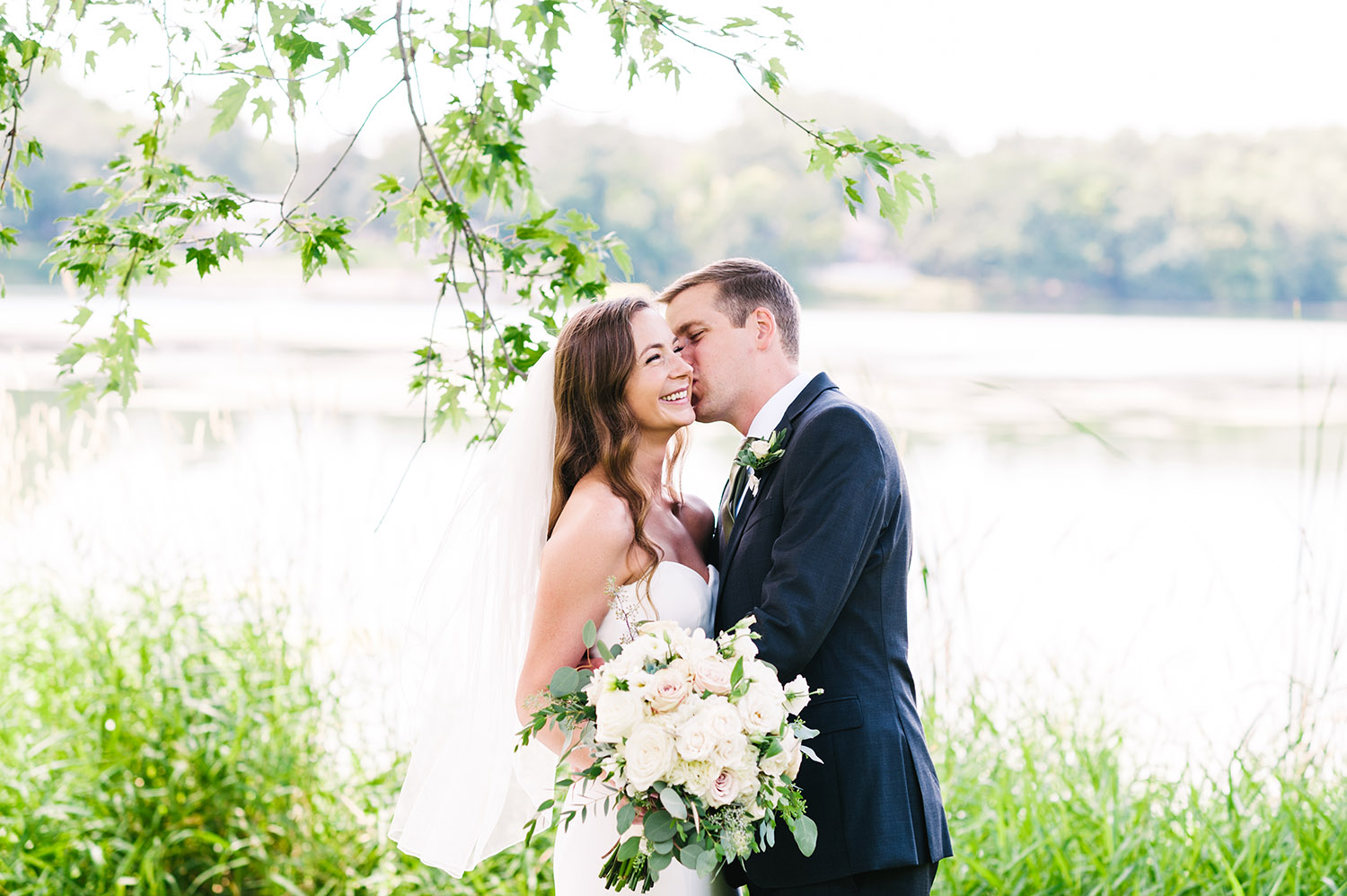bride and groom in front of a lake