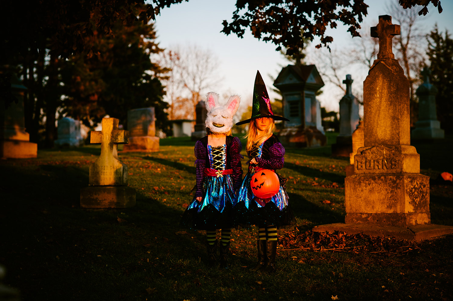 two young girls dressed as witches in a graveyard