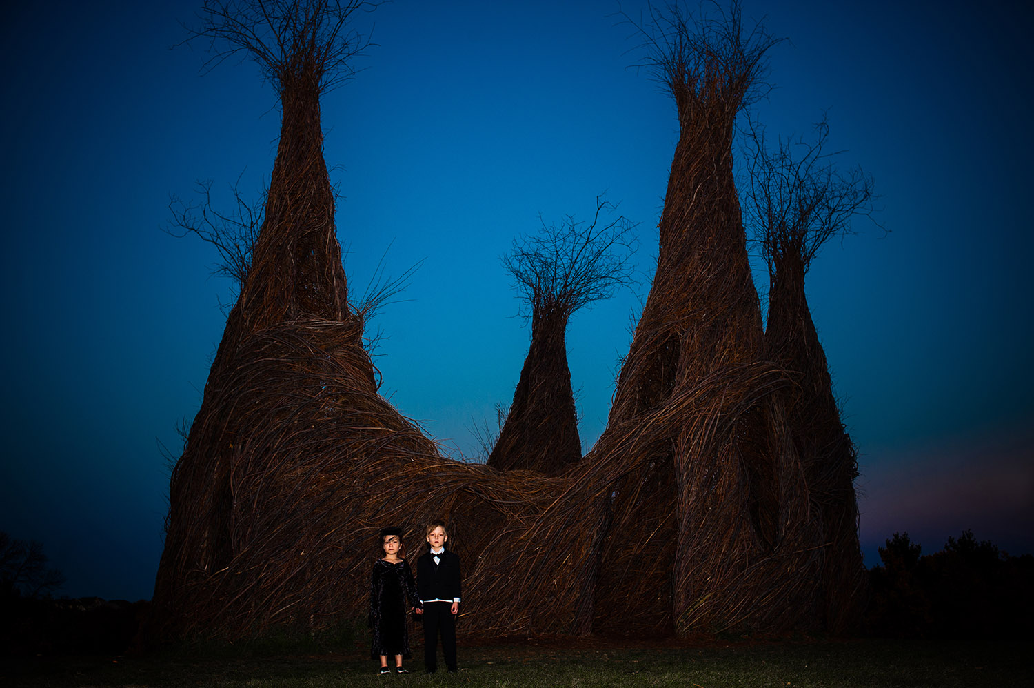 girl and boy twins dressed in black spooky attire in front of stick sculpture